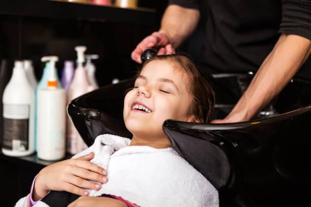 kleines mädchen waschen haare bei friseur - mädchen dusche stock-fotos und bilder