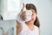 istock Little girl washing hands with water and soap in bathroom. 1214532024