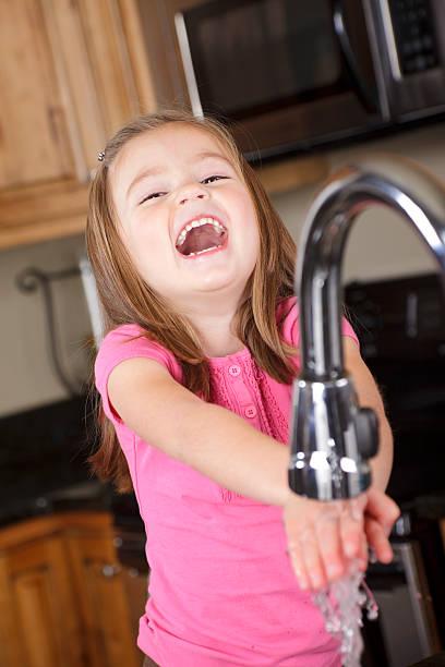 kleines mädchen waschen ihre hände - hände wasser wasserhahn kinder lachen stock-fotos und bilder
