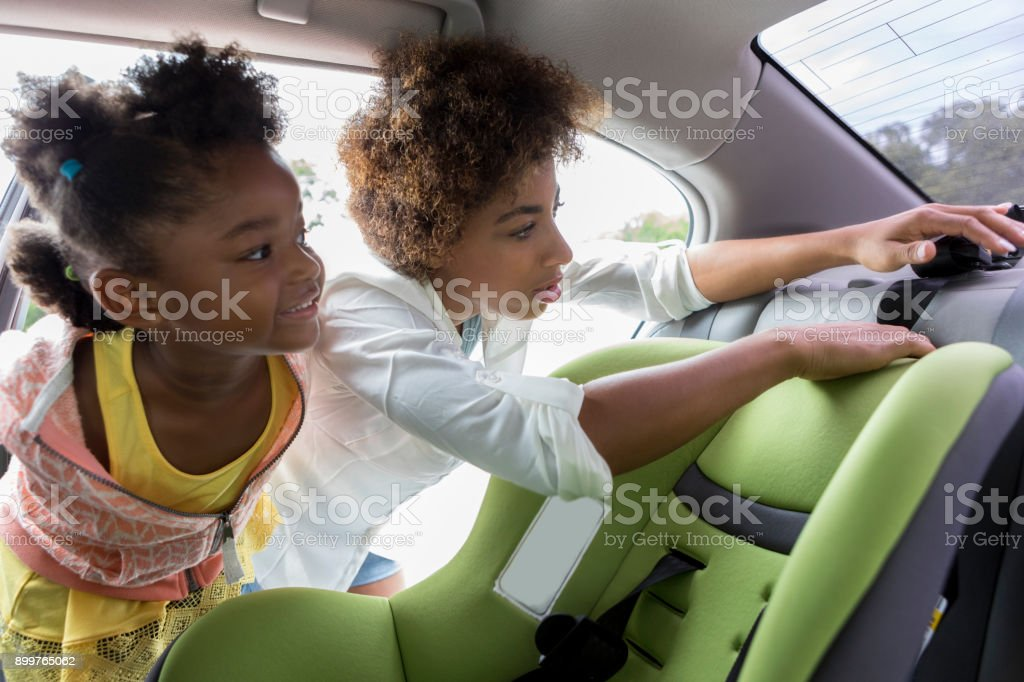 Little girl watches mother install car seat stock photo