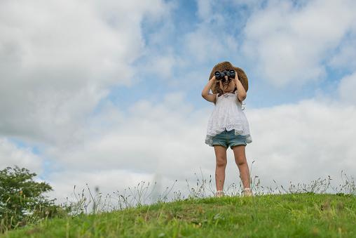 Little girl watching binoculars