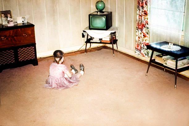 kleines mädchen vor dem ersten fernseher, retro-vintage-stil - mädchenraum vorhänge stock-fotos und bilder