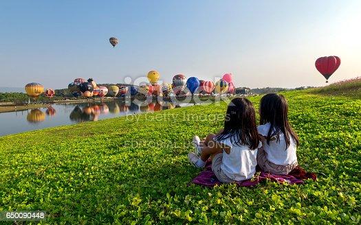 istock Little girl Watching Hot Air Balloon at Singha Park  Chiang Rai Balloon Fiesta, Thailand 650090448