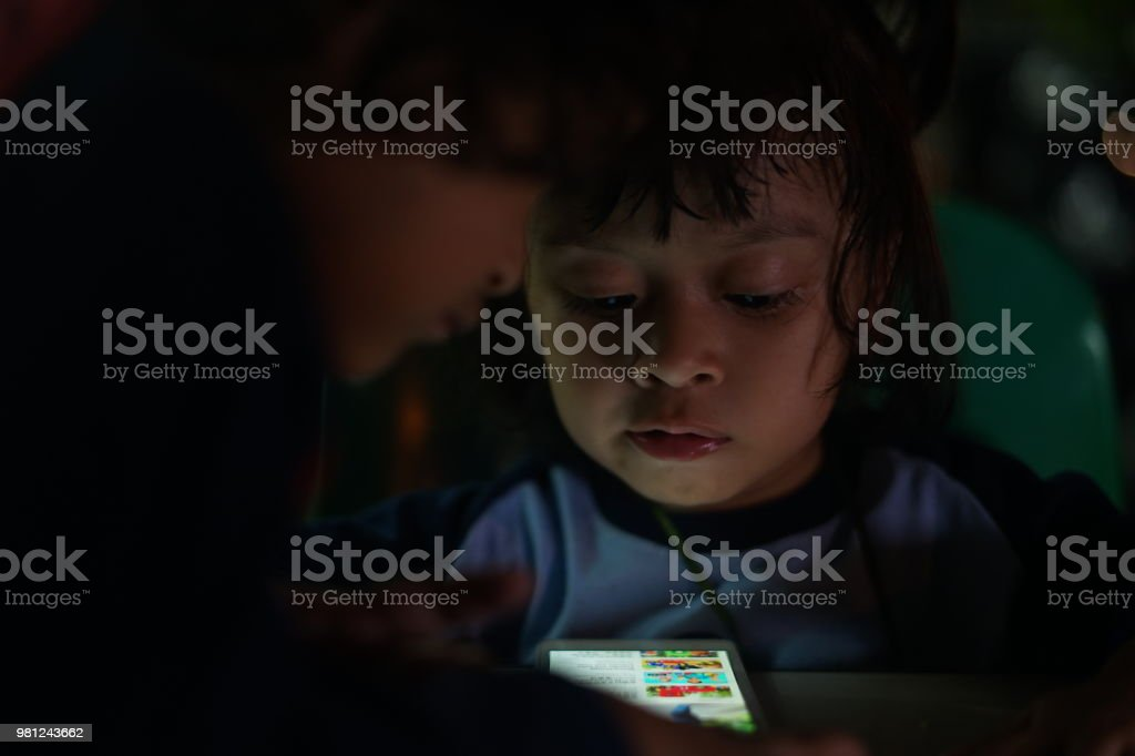 Little Girl Watching Movies On A Smartphone At Coffee Shop