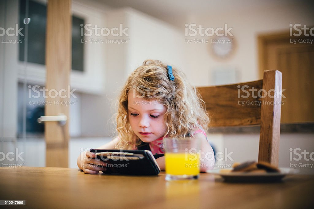 Little Girl Watching TV on a Smartphone stock photo