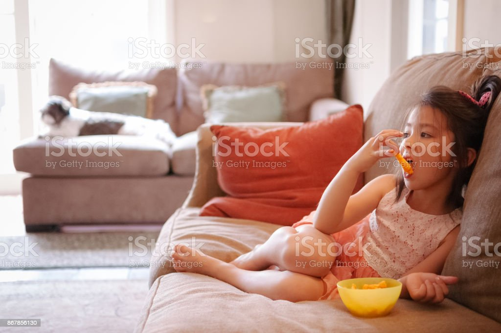 Little girl watching TV while eating cheese puffs at home - Royalty-free 6-7 Years Stock Photo
