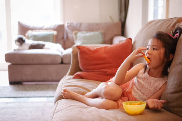Little girl watching TV while eating cheese puffs at home stock photo