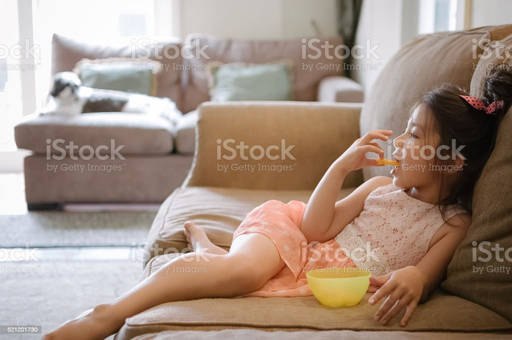 Little girl watching TV while eating snack at home royalty-free stock photo