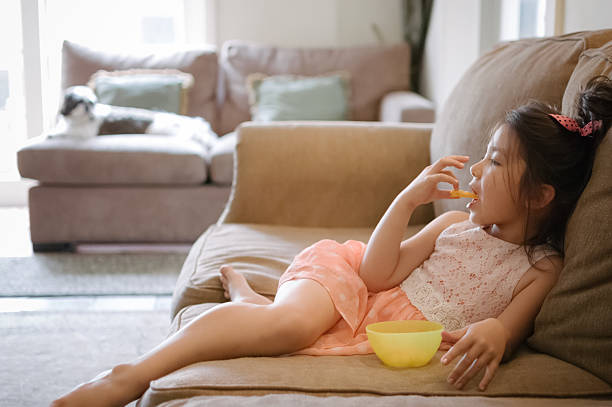 Little girl watching TV while eating snack at home stock photo