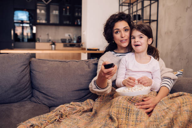 Little girl watching TV with mom stock photo