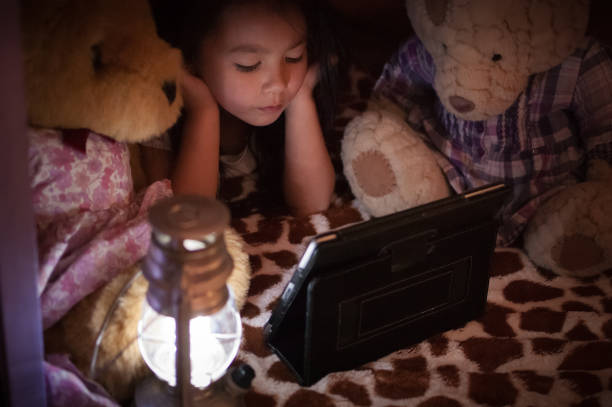 Little girl watching video on tablet with teddy bears stock photo