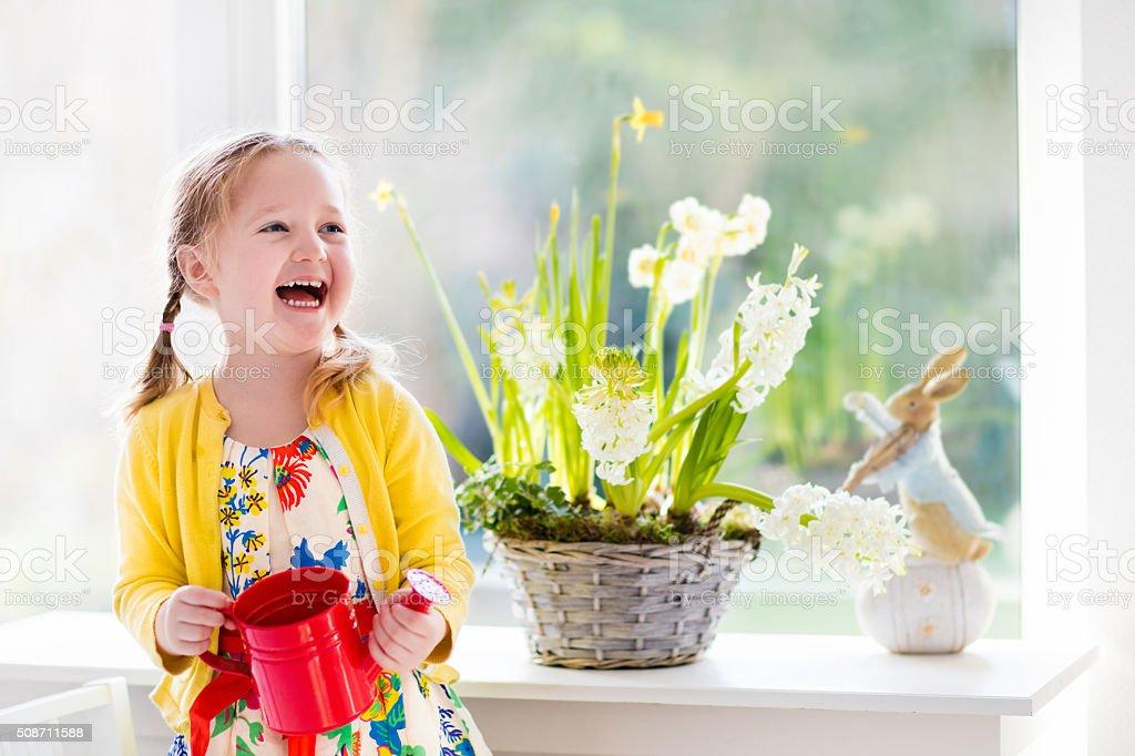 Little girl watering Easter flowers stock photo
