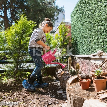 Little girl watering fresh planted cactus flowers