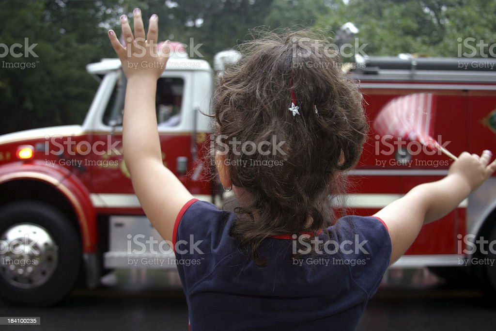 Little Girl Waves at Patriotic Parade stock photo