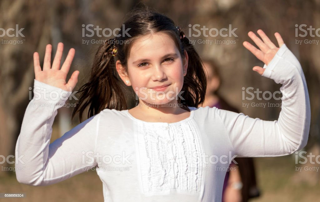 Little girl waving in park during the sunny spring day stock photo