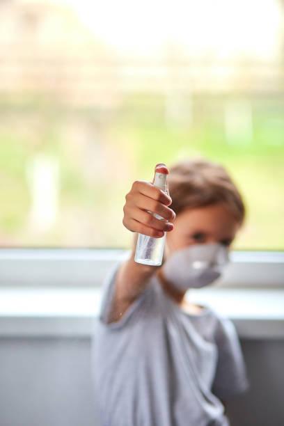Kleines Mädchen tragen hygienische Maske und drücken Alkoholspray zu schützen, desinitiieren. – Foto