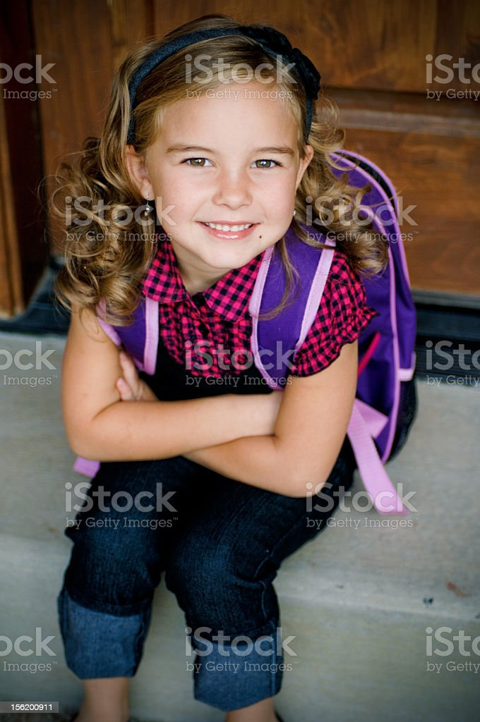A little girl wearing a backpack royalty-free stock photo