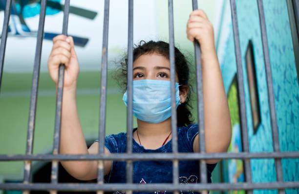 Kleines Mädchen trägt eine Gesichtsmaske und guckt aus dem Fenster – Foto