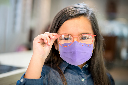 Portrait of a little Latin American girl wearing a facemask while trying glasses at the optician – illness prevention concepts