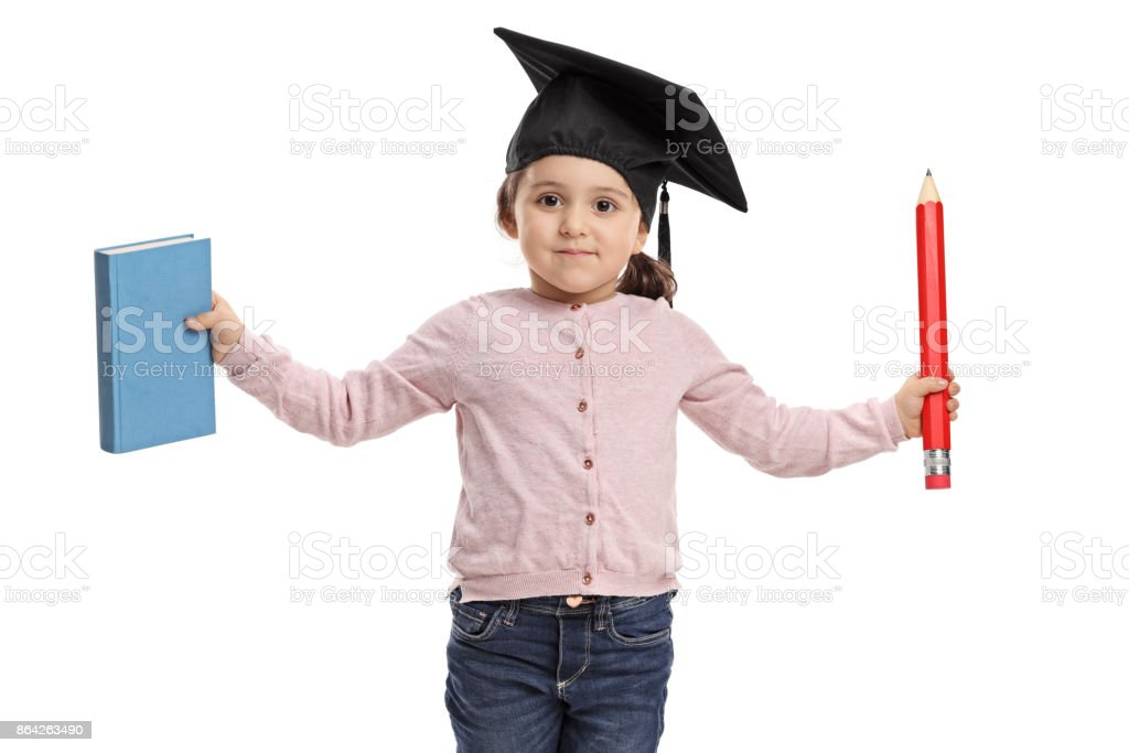Little girl wearing a mortarboard holding a book and a pencil royalty-free stock photo
