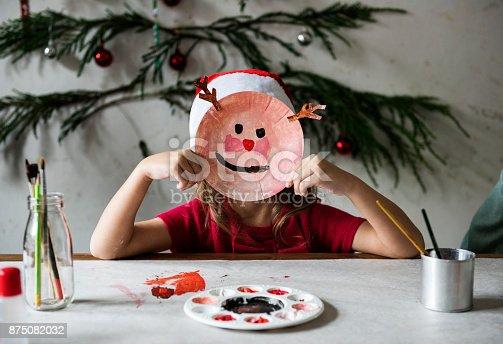 istock Little girl wearing a reindeer mask 875082032