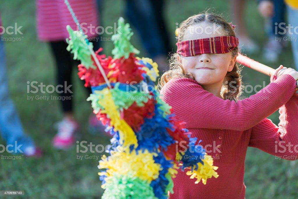Little girl wearing blindfold hitting a pinata stock photo