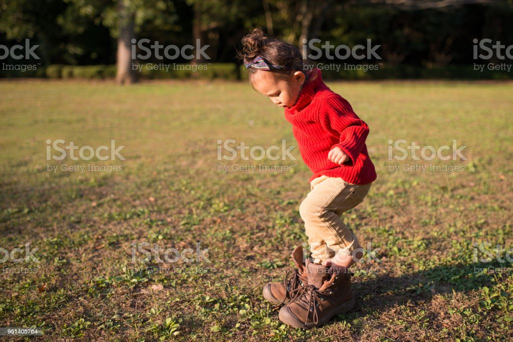 Little girl wearing boots that are too big stock photo