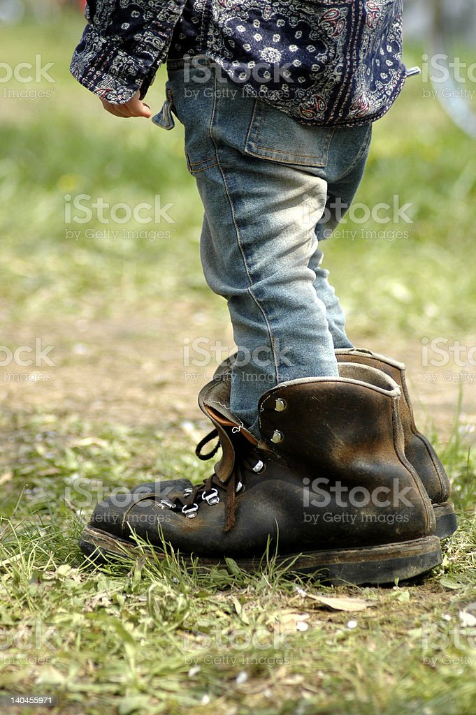 Little girl wearing boots too big for her stock photo