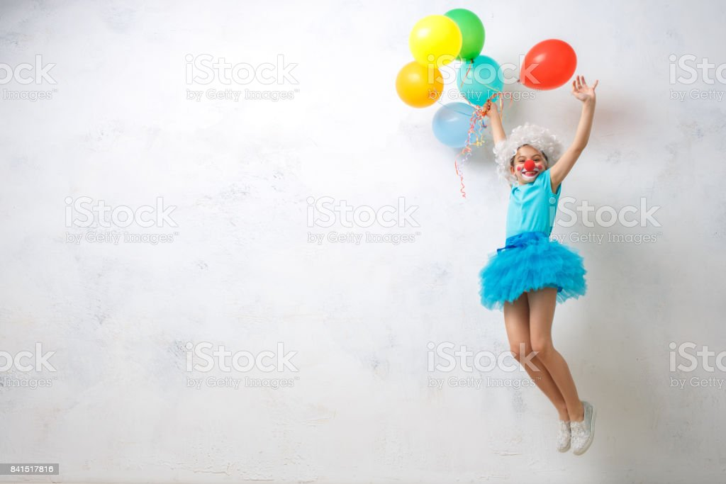 Little girl wearing clown costume isolated on white stock photo