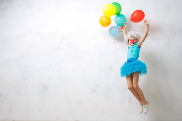 Little girl wearing clown costume isolated on white Little child wearing clown costume birthday celebration with balloons carnival children stock pictures, royalty-free photos & images