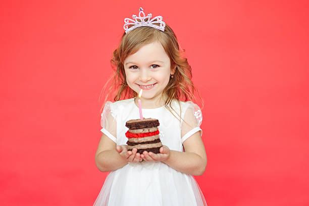 kleines mädchen mit krone halten geburtstagstorte - prinzessinnen torte stock-fotos und bilder