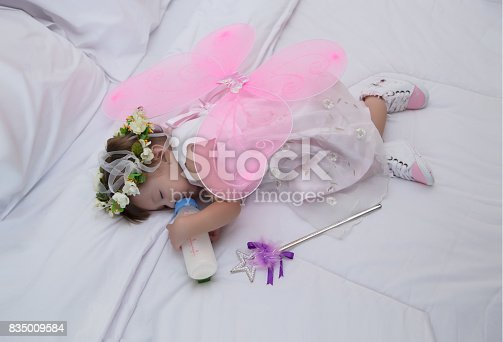 istock Little girl wearing dresses pink with angel wings, sleeping, eating milk on a white bed. 835009584