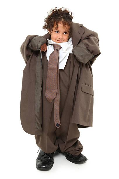 little girl wearing grown up man's business suit - te groot stockfoto's en -beelden