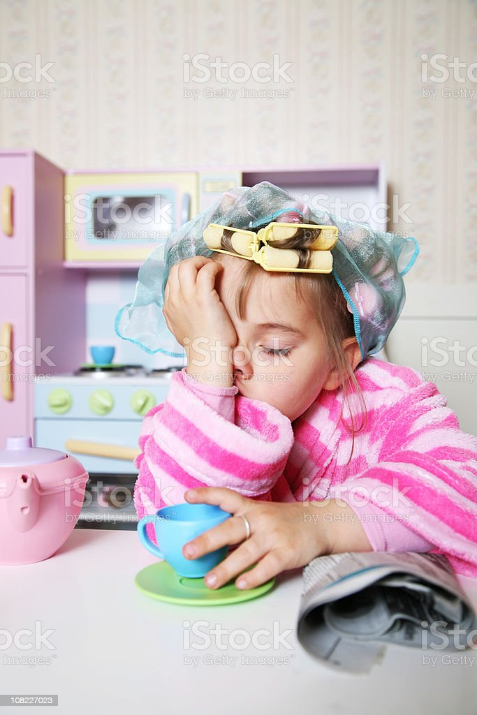 Little Girl Wearing Hair Rollers and Bathrobe at Toy Table royalty-free stock photo