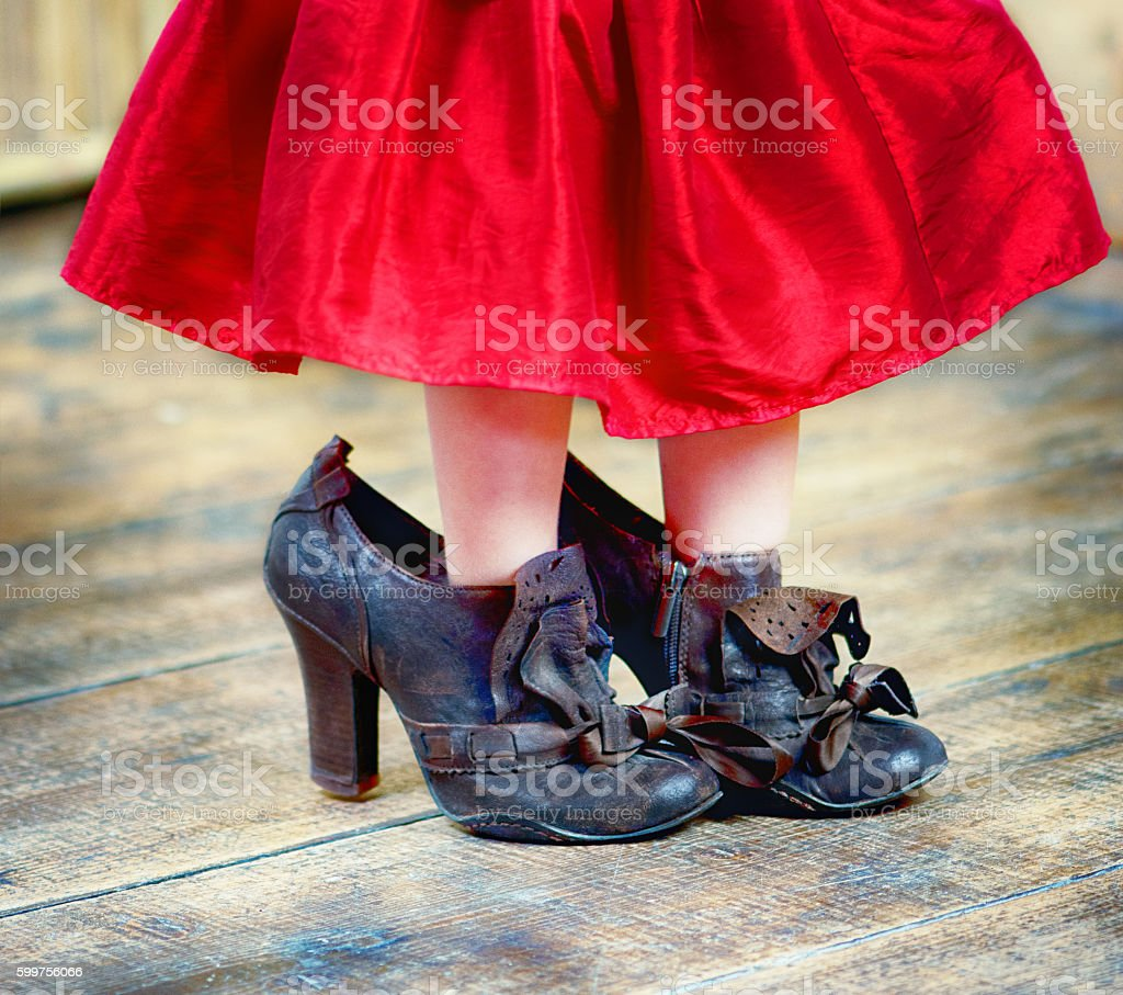 Little girl wearing her mother's high hells shoes - foto stock