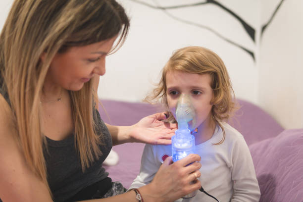 Little Girl Wearing Inhaling Mask Mother Hold Young little girl and using Inhaling mask to relieve the cough respiratory disease stock pictures, royalty-free photos & images