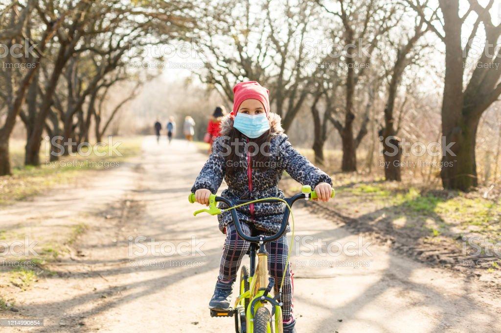 Niña que lleva máscara médica prevenir la gripe, la contaminación y la ovivida-19 montando en bicicleta al aire libre. - Foto de stock de Accesorio de cabeza libre de derechos