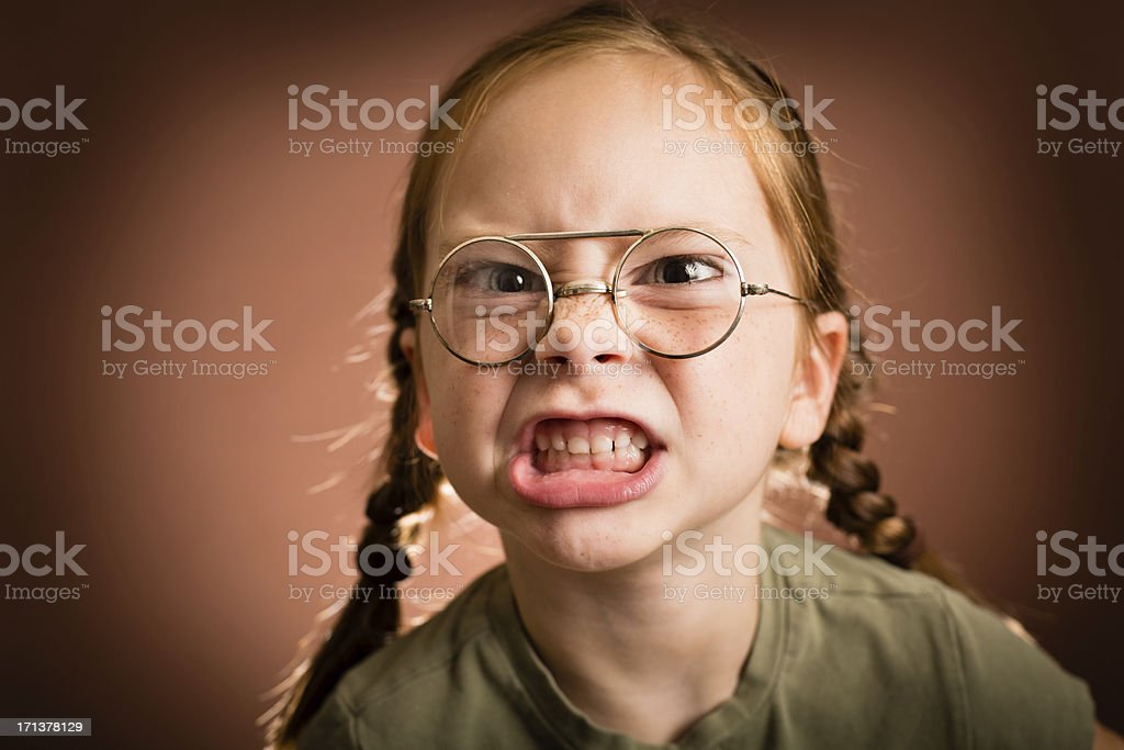 "Little Girl Wearing Nerdy Glasses Making a Mean Face ""Color image of a young girl with red hair, wearing nerd glasses and making a mean face, with brown background."" 6-7 Years Stock Photo"