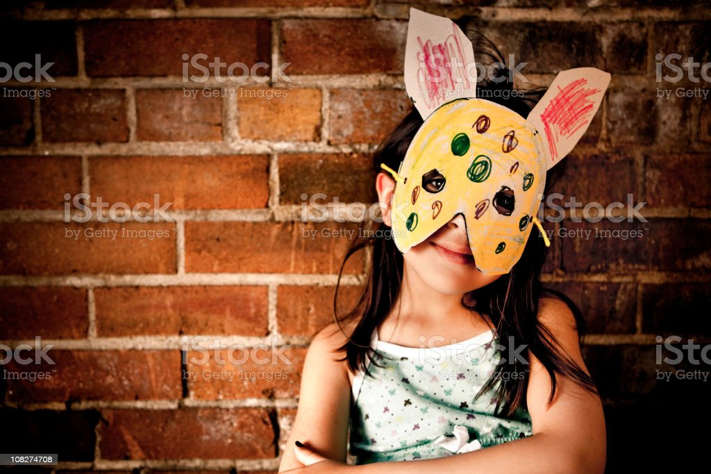 Little girl wearing paper bunny mask stock photo