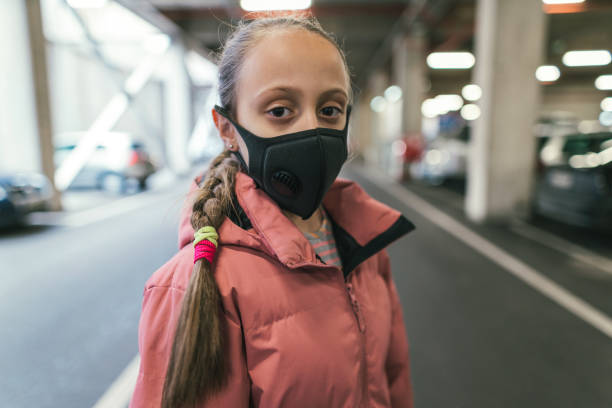 Little girl wearing protective face mask in public setting stock photo
