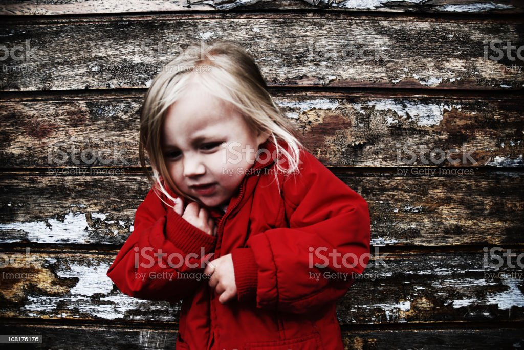 Little Girl Wearing Red Coat Against Grunge Wooden Background royalty-free stock photo