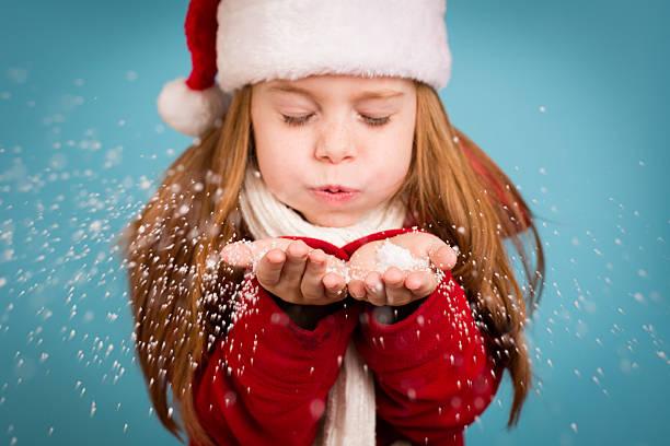 kleines mädchen mit santa hut und blasen handvoll schnee - weihnachten 7 jährige stock-fotos und bilder