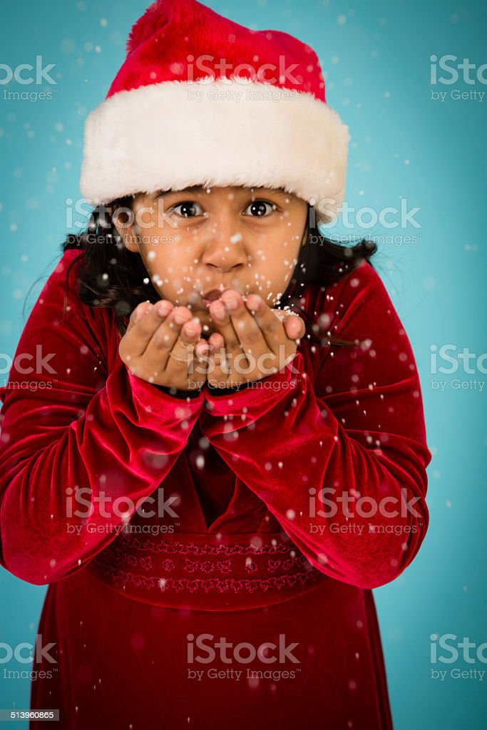 d2df416b209e9 Little Girl Wearing Santa Hat and Blowing Handful of Snow - Stock image .