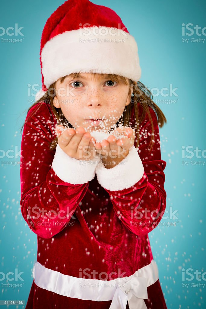 2c3765f742e7d Little Girl Wearing Santa Hat and Blowing Handful of Snow royalty-free stock  photo