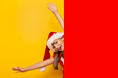 Beautiful little girl wearing Santa hat jumping out behind huge blank red cardboard sheet isolated on yellow colored background with copy space