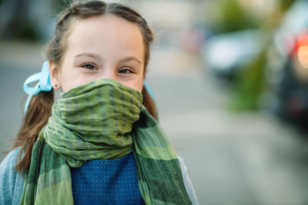 Little girl wearing scarf as protective measure during COVID-19
