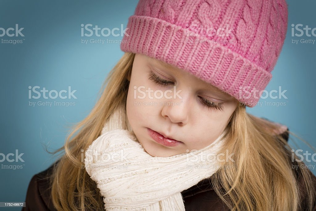 Little Girl Wearing Warm Clothes and Looking Sad royalty-free stock photo