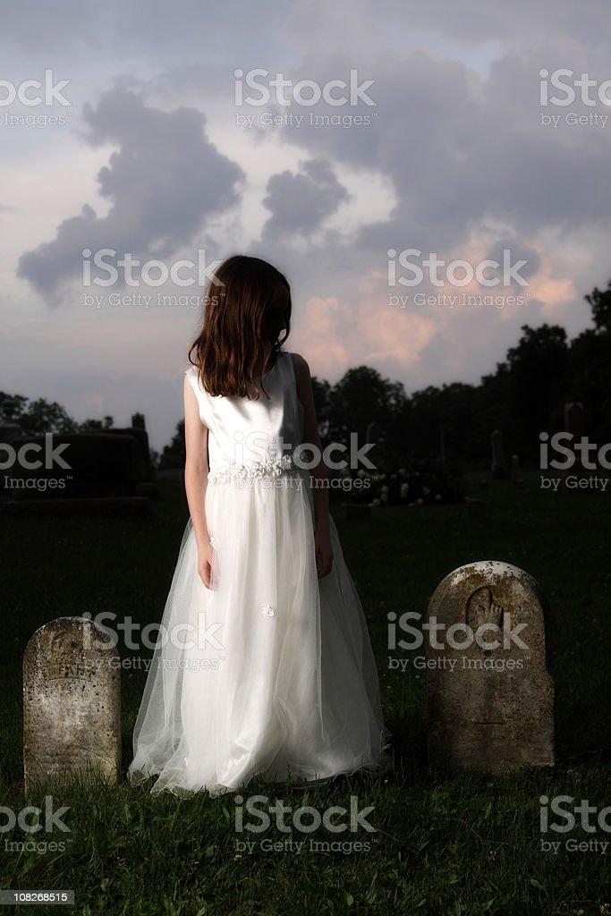 Little Girl Wearing White Dress in Graveyard royalty-free stock photo