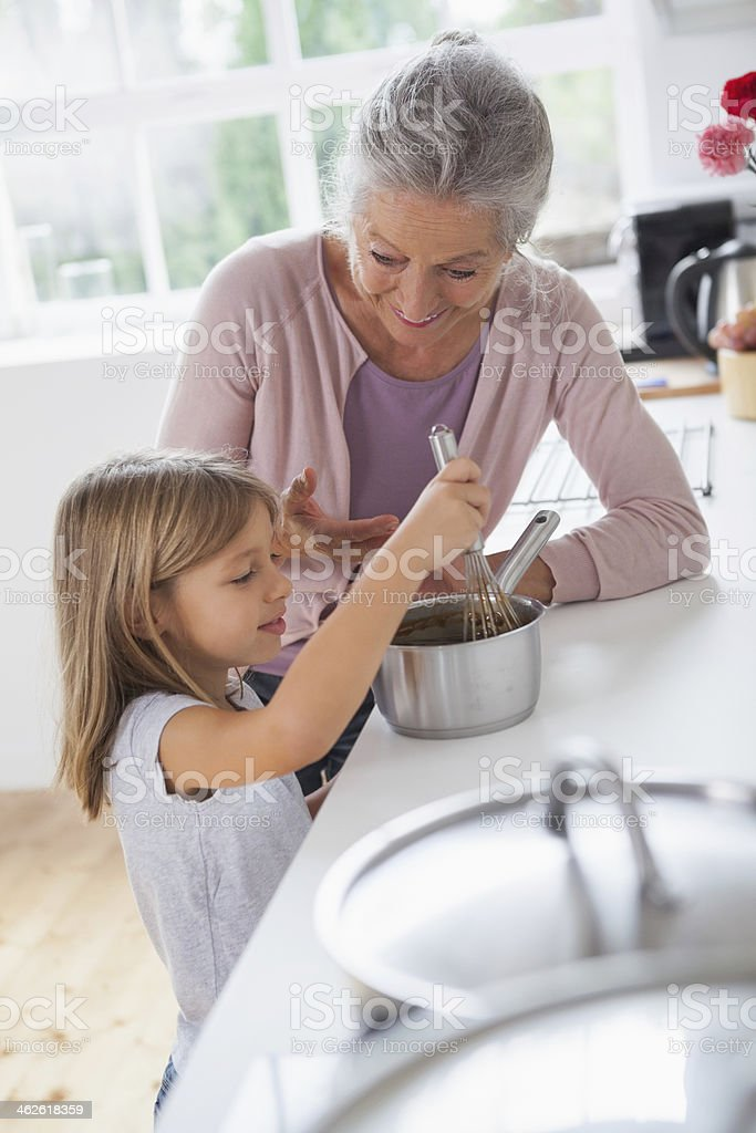 Little girl whisking chocolate sauce with granny royalty-free stock photo