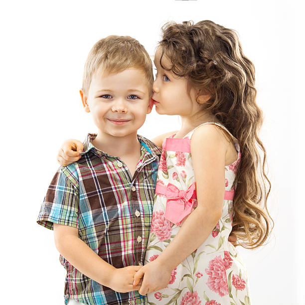 little girl whispering something to boy - little girls little boys kissing love stock photos and pictures